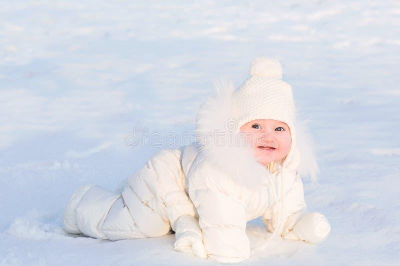 Милый младенец в белом костюме меха вползая в снеге на очень солнечный зимний день стоковое изображение