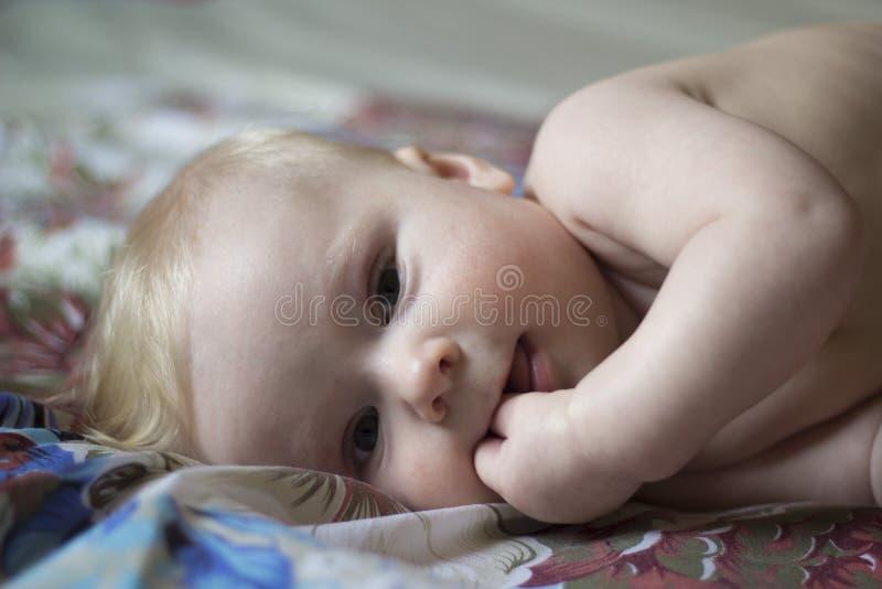 Милый младенец лежа на кровати с пальцами в его рте стоковые изображения