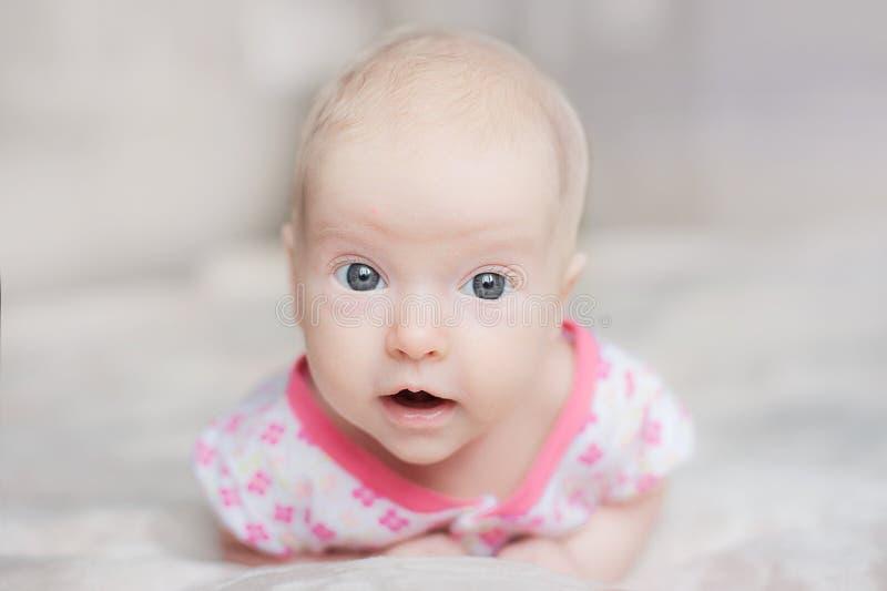 Милый младенец на белой кровати стоковое фото rf