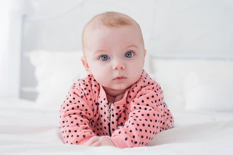 Милый младенец на белой кровати стоковое фото
