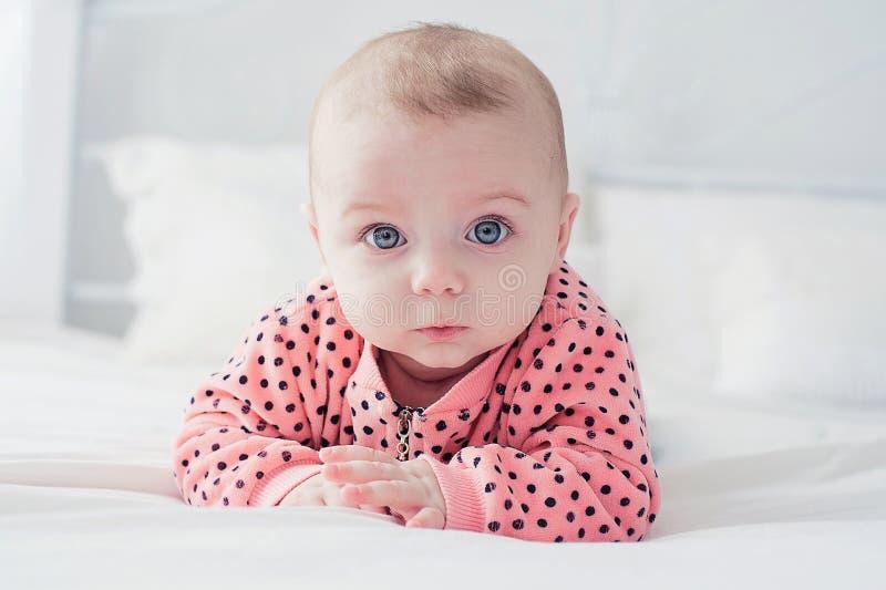Милый младенец на белой кровати стоковая фотография