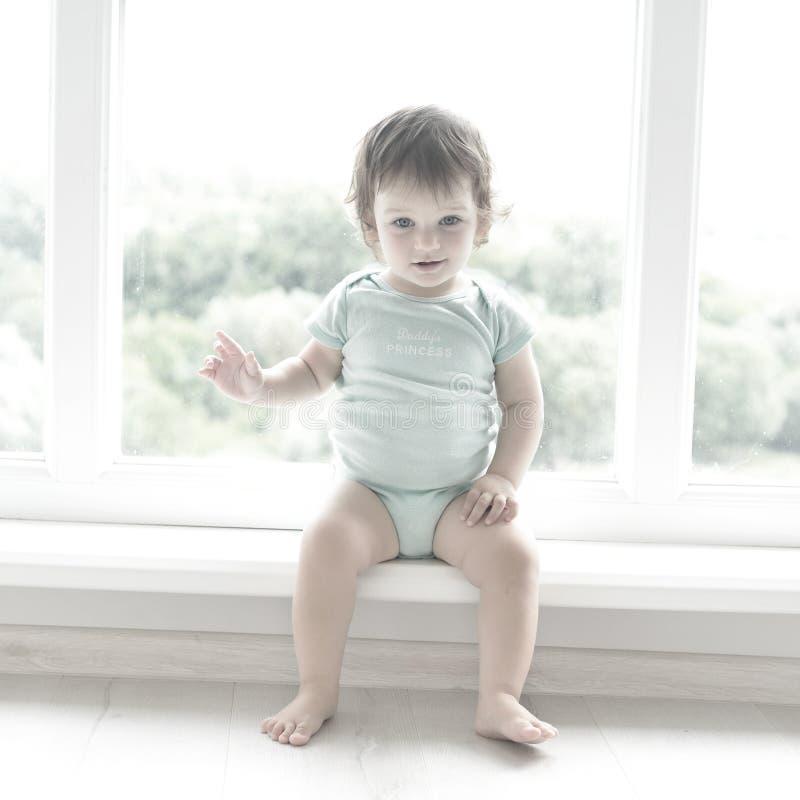 Милый младенец дома в белой комнате сидит около окна Красивый младенец смог быть мальчиком или девушкой и носит костюм тела стоковые изображения