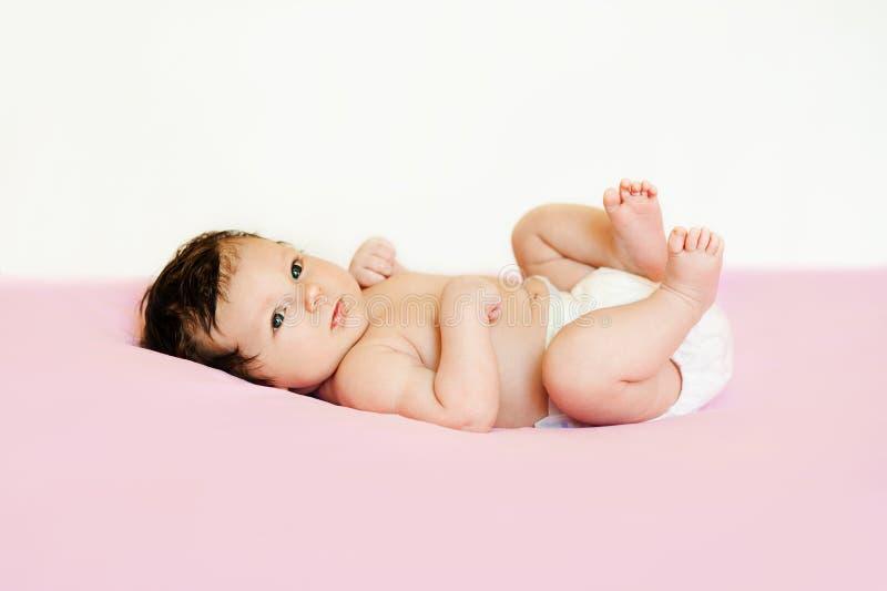 Милый младенец пеленки лежа на его ноги задней части и повышений вверх стоковая фотография