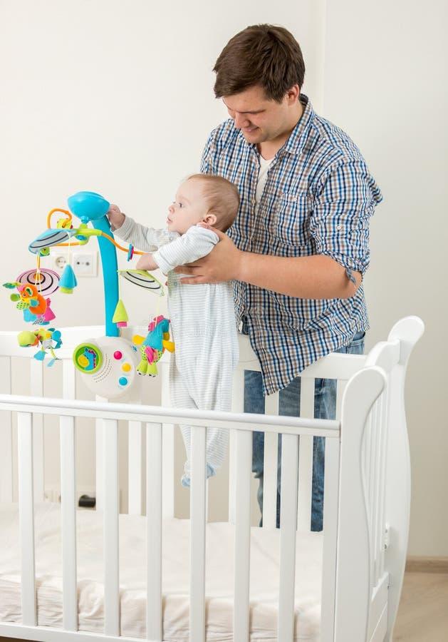 Милый младенец стоя в кроватке и играя с carousel с его салом стоковые фото
