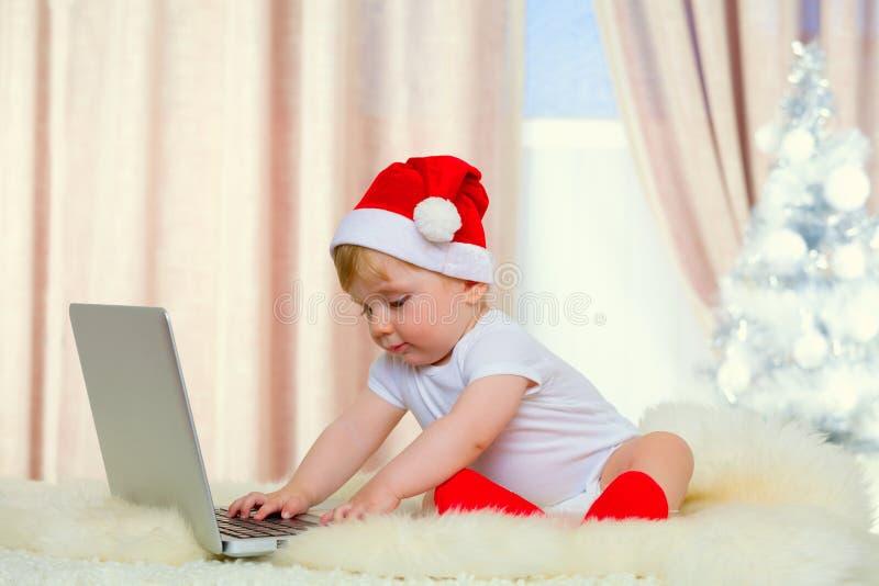 Милый младенец santa с компьтер-книжкой стоковые изображения rf