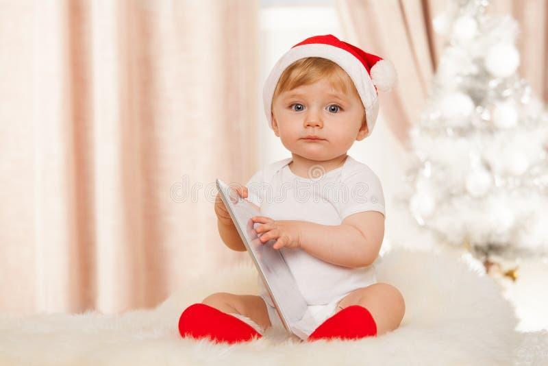 Милый младенец santa с таблеткой стоковые фотографии rf