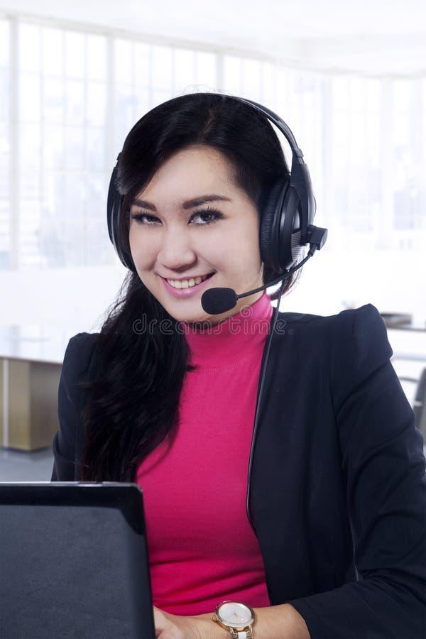 Милый оператор центра телефонного обслуживания работая в офисе стоковое изображение rf