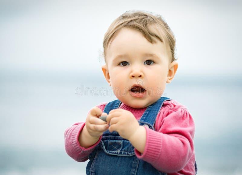 Милый одногодичный ребенок играя с камешками стоковые фото