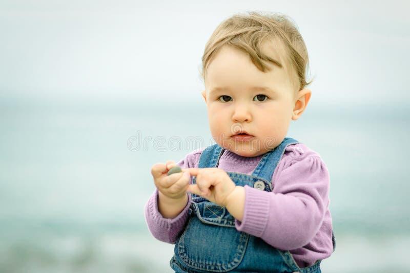 Милый одногодичный старый младенец играя на пляже стоковые изображения rf