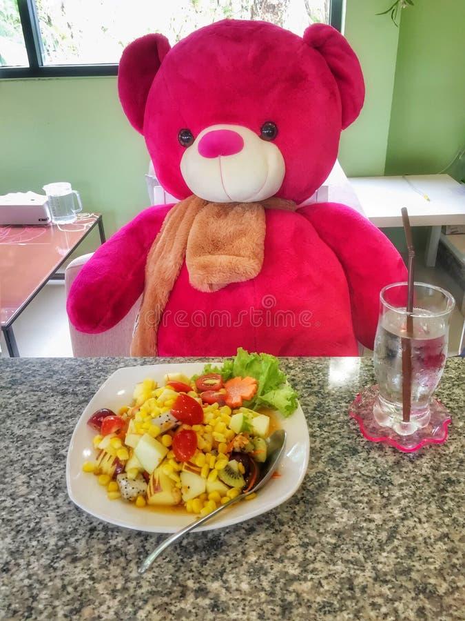 Милый плюшевый медвежонок есть vegetable салат стоковые изображения