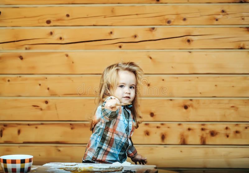 Милый ребенок варя с тестом, мукой держит деревянный лопаткоулавливатель стоковое фото rf