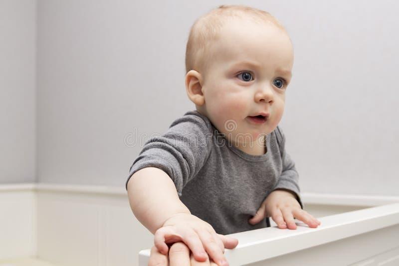 Милый ребёнок в шпаргалке Прелестный младенческий ребенк оставаясь в кроватке стоковое изображение rf