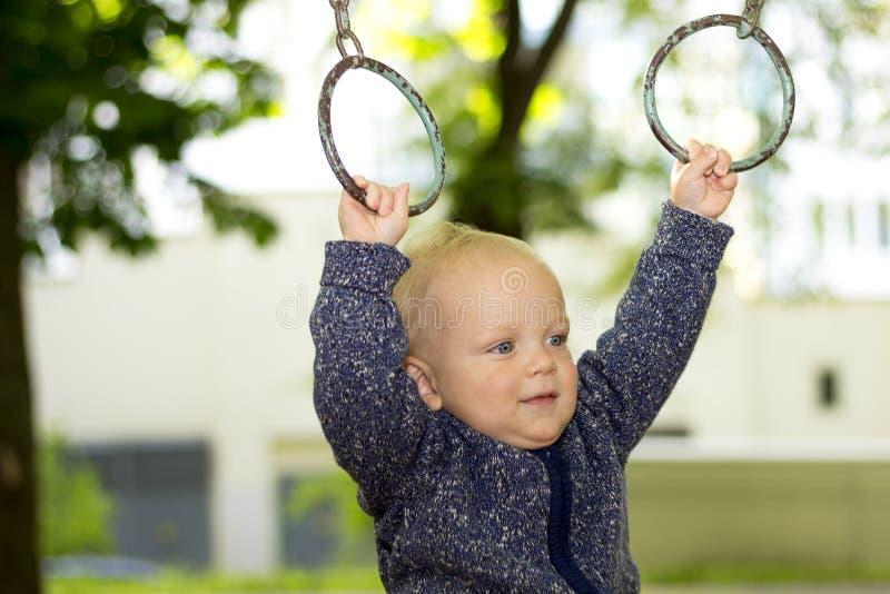 Милый ребёнок делая спорт в парке Смешные разминки малыша на атлетических кольцах стоковые изображения