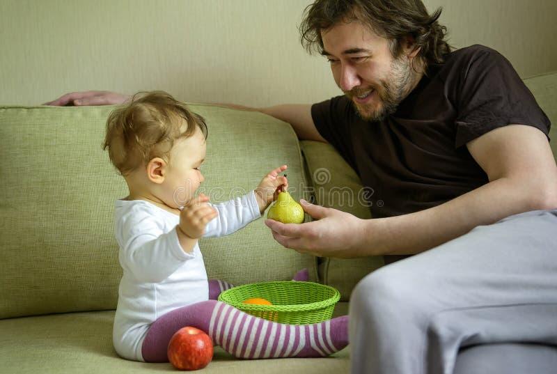 Милый ребёнок играет с плодоовощами с ее отцом дома стоковые фото