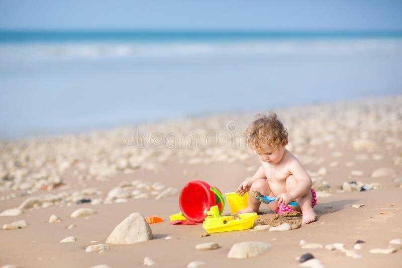 Милый ребёнок играя с песком на красивом пляже стоковая фотография