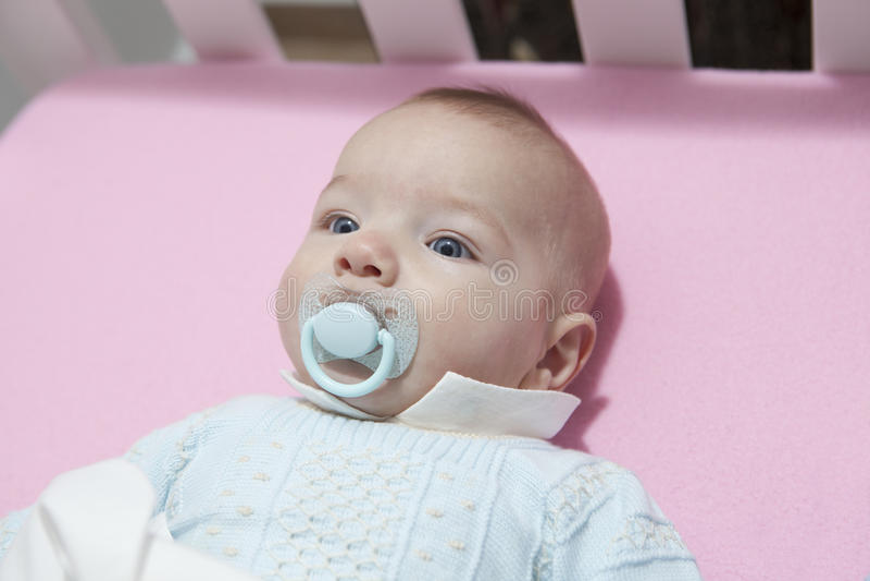 Милый ребёнок 4 месяцев лежа в кроватке с pacifier стоковое фото rf