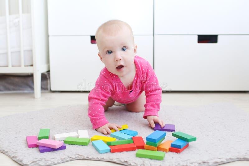 Милый ребёнок 6 месяцев играет деревянное пестротканое meccano стоковое изображение