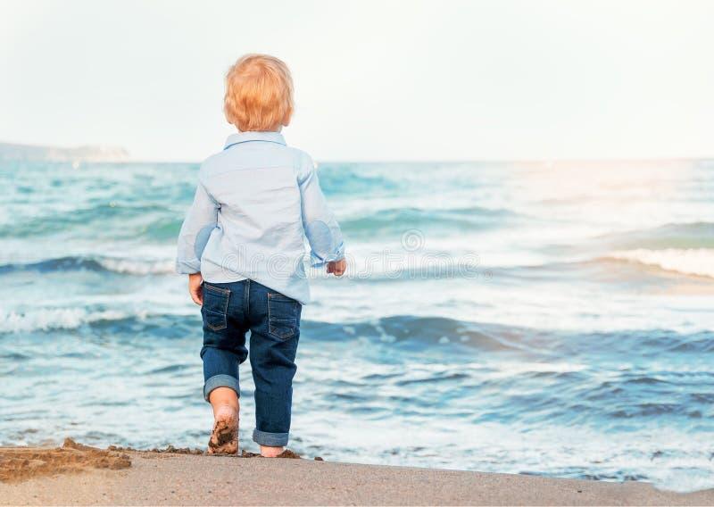 Милый ребёнок на пляже, восхищая море чуть-чуть ноги Счастливый стоковые изображения rf