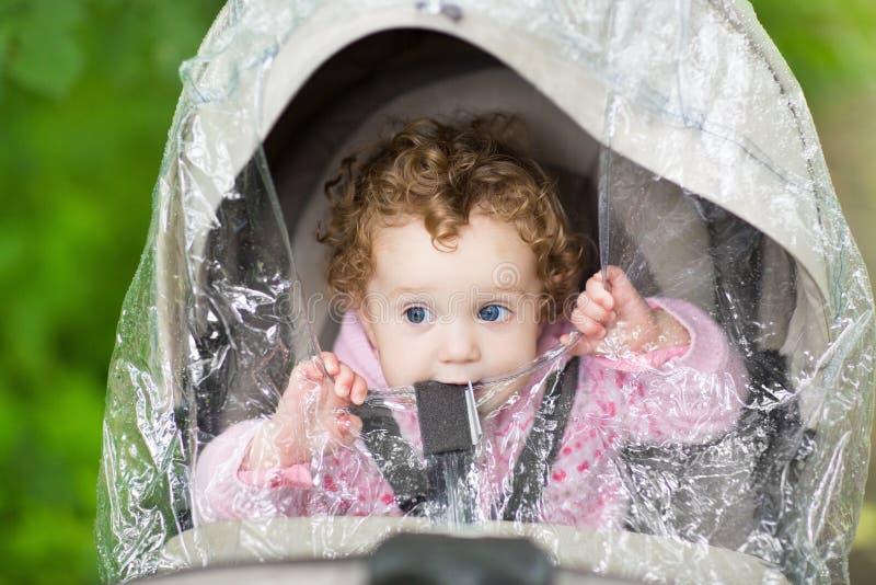 Милый ребёнок сидя в прогулочной коляске под пластичным дождем стоковое фото rf