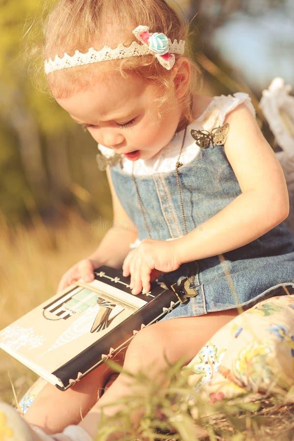 Милый ребёнок читая outdoors стоковая фотография