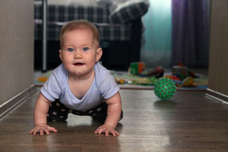 Милый счастливый младенец вползая на поле стоковое изображение rf