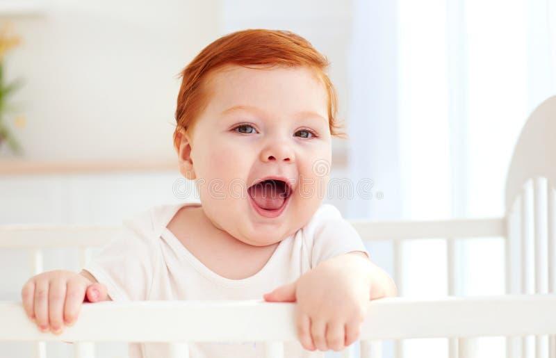 Милый счастливый младенческий младенец стоя в кроватке дома стоковое фото rf