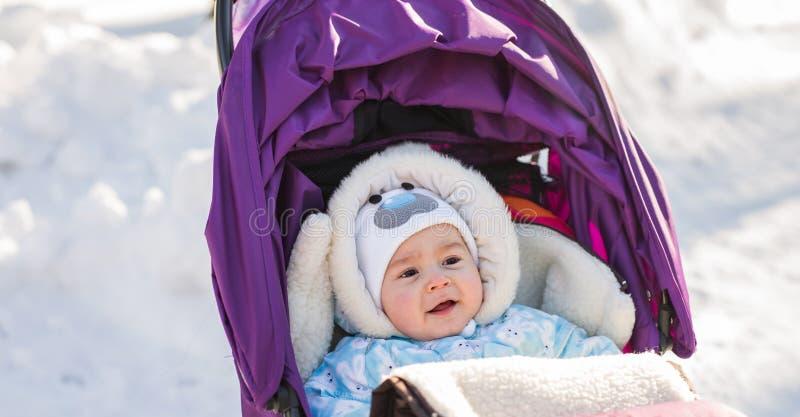 Милый усмехаясь младенец сидя в прогулочной коляске на холодный зимний день стоковая фотография