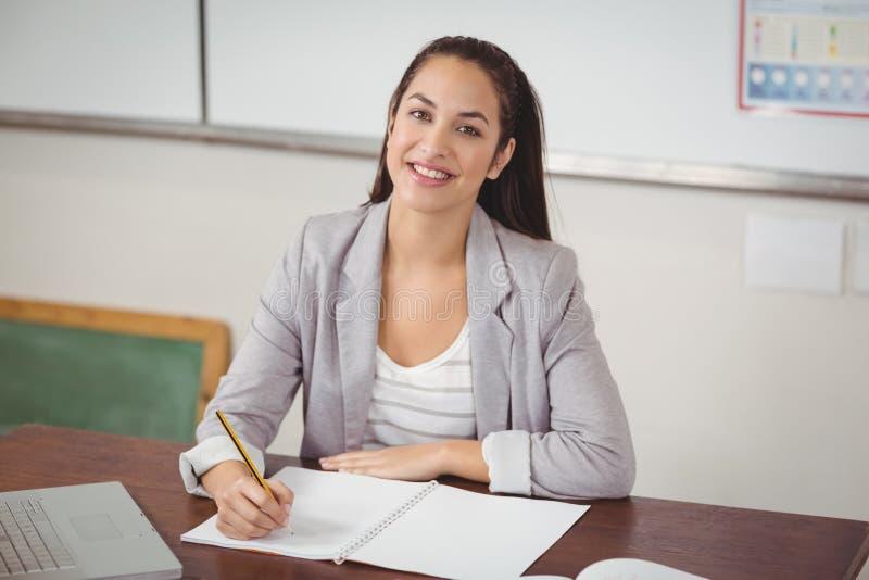 Милый учитель исправляясь на ее столе в классе стоковые изображения rf