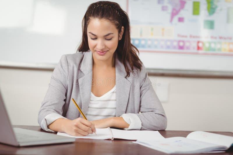 Милый учитель исправляясь на ее столе в классе стоковые фото