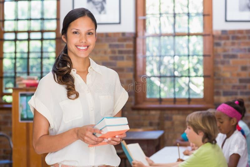 Милый учитель усмехаясь на камере в библиотеке стоковое изображение