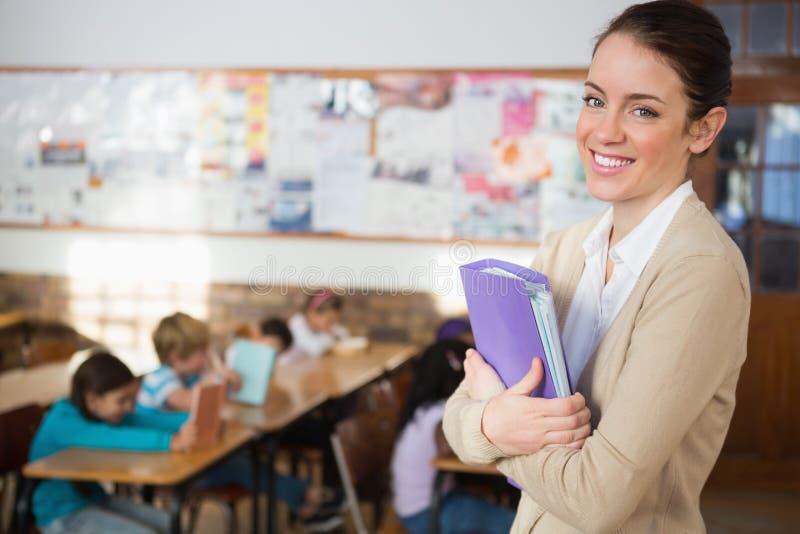 Милый учитель усмехаясь на камере на задней части класса стоковое фото