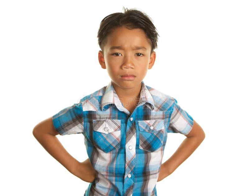 Милый филиппинский мальчик на белой предпосылке и сердитом выражении стоковое изображение