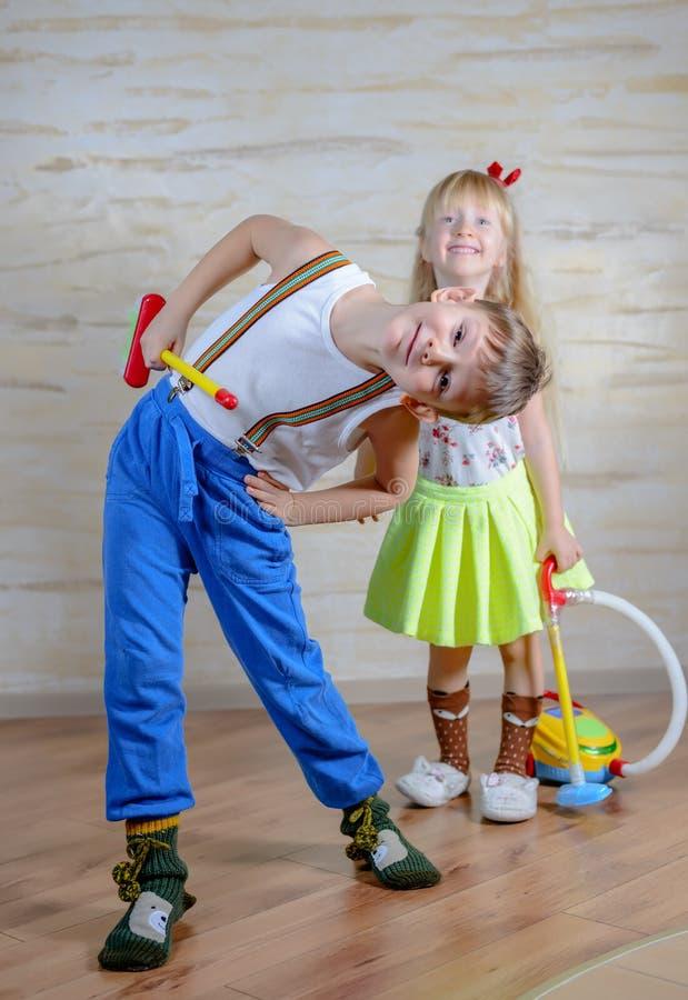 Милый шаловливый дом чистки мальчика и девушки стоковые фото