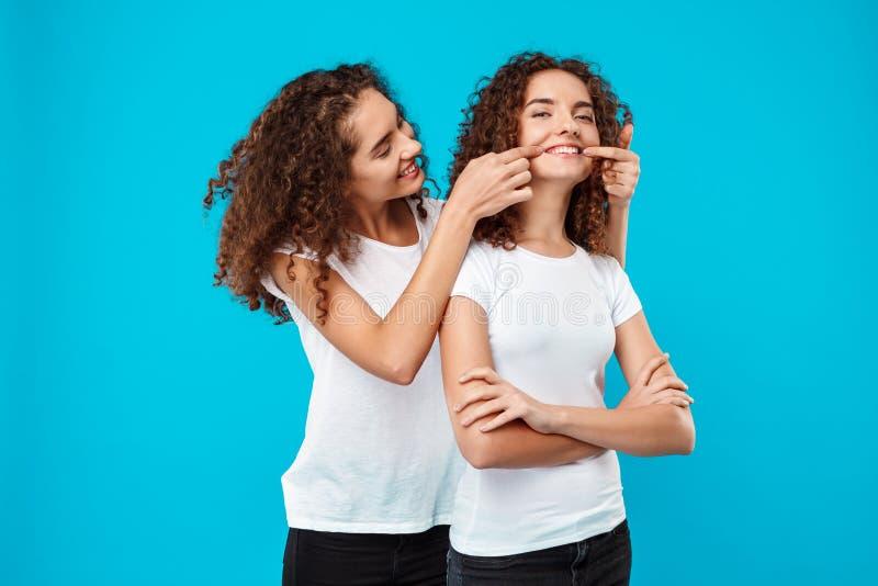 2 милых близнеца девушек усмехаясь, шутящ над голубой предпосылкой стоковое фото rf