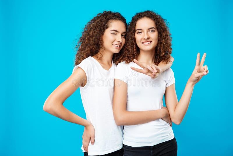 2 милых близнеца усмехаться девушек, показывая мир над голубой предпосылкой стоковое фото rf