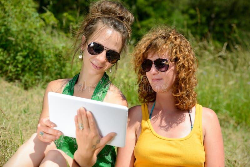 Download 2 милых девушки на траве с цифровой таблеткой Стоковое Фото - изображение насчитывающей река, усаживание: 41661540