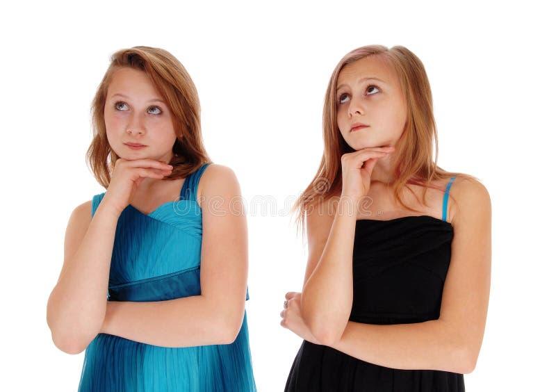 2 милых девушки думая крепко стоковая фотография