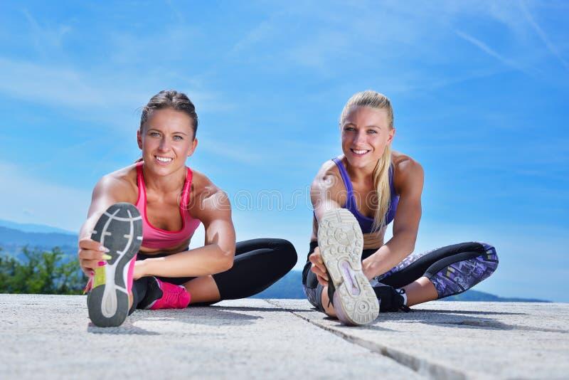 Download 2 милых женщины протягивая в парке перед начинать встречу разминки Стоковое Фото - изображение насчитывающей холм, земля: 81801552