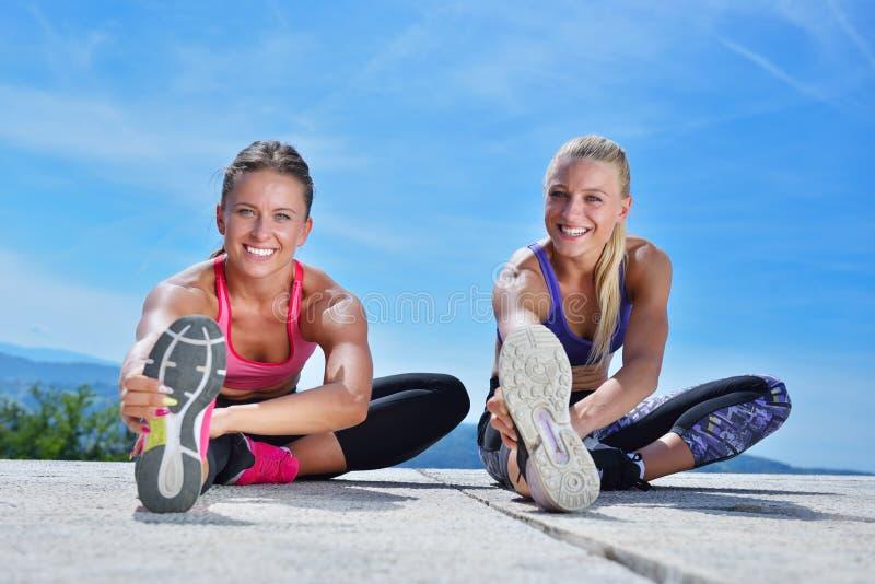 Download 2 милых женщины протягивая в парке перед начинать встречу разминки Стоковое Фото - изображение насчитывающей бегунок, тренировка: 81801898