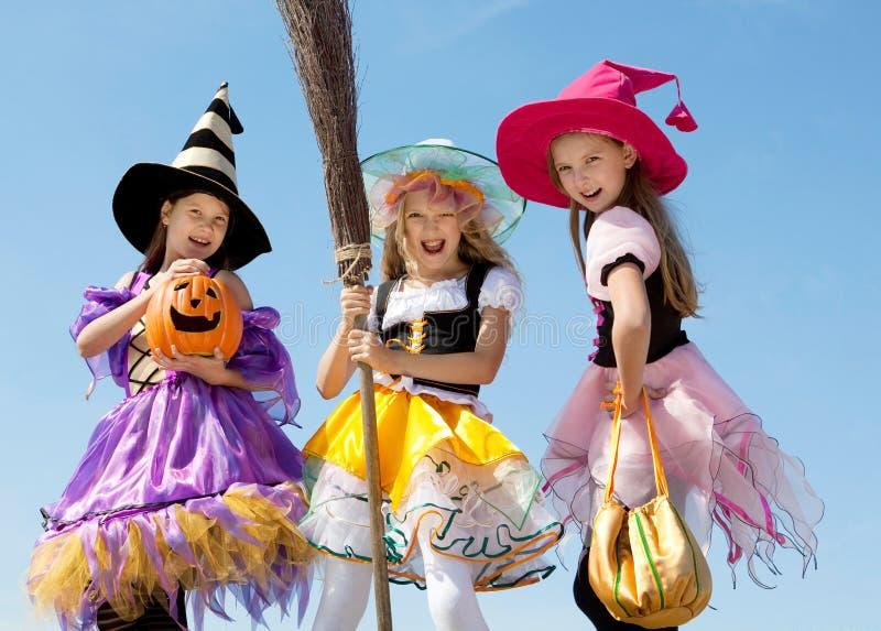 3 милых маленьких ведьмы стоя с веником стоковые фото