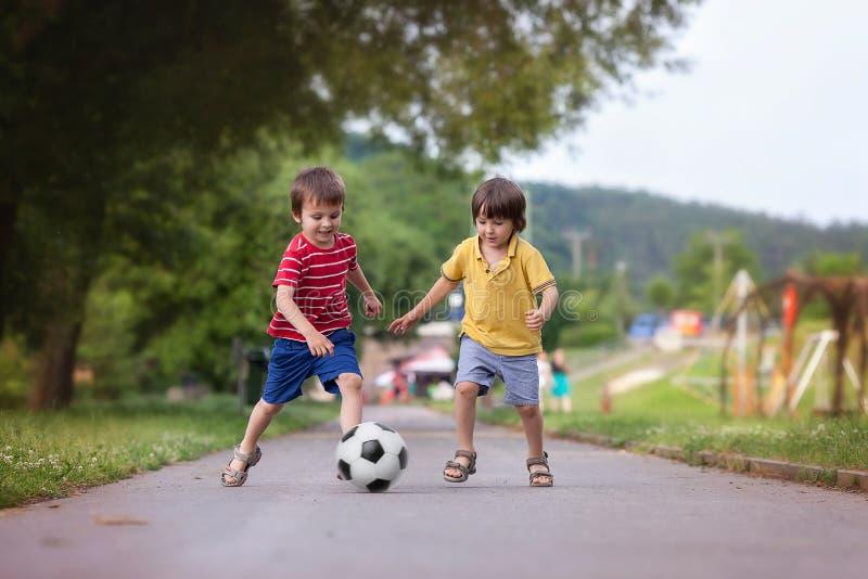 2 милых маленького ребенка, играя футбол совместно, летнее время стоковое изображение rf
