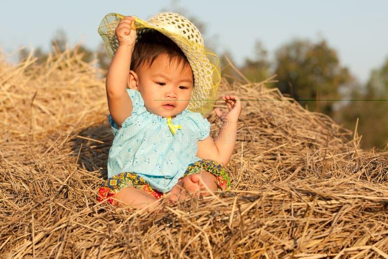 младенец Азии сидит сторновка стоковая фотография