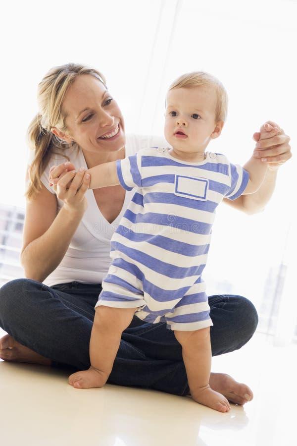 младенец внутри помещения будет матерью играть стоковое изображение