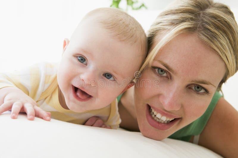 младенец внутри помещения будет матерью усмехаться стоковая фотография