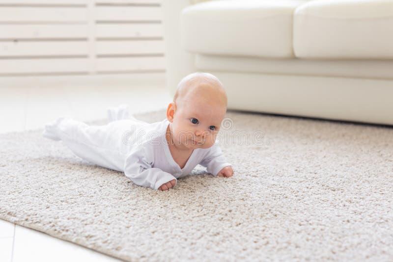 Младенец, детство, концепция людей - портрет вползая младенца на поле стоковая фотография