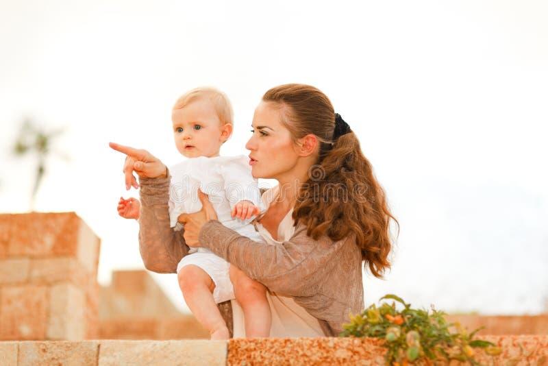 младенец ее заинтересованная мать показывая что-то стоковая фотография