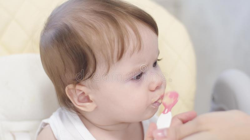 Младенец ест кашу от ложки, вертелов и улыбок сидя на высоком стульчике в кухне стоковое изображение