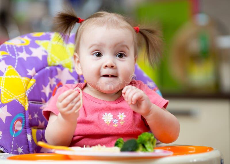 Младенец ест макаронные изделия при овощи сидя в высоком стульчике в кухне стоковое фото