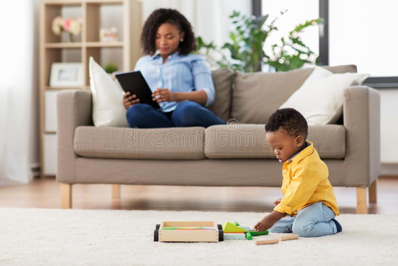 Младенец играя блоки и мать игрушки используя ПК планшета стоковые фотографии rf