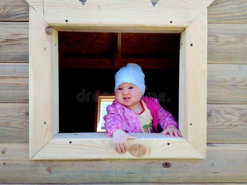 Младенец играя в деревянном доме стоковое изображение rf